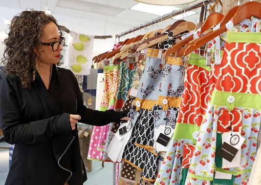Alexis A Trembone, founder and owner of The Bedford Life, shows the aprons she makes during the Meet the Makers event at Domestic Dry Goods Company, where everything is made in America in Rye Brook. (Photo: Tania Savayan/The Journal News)
